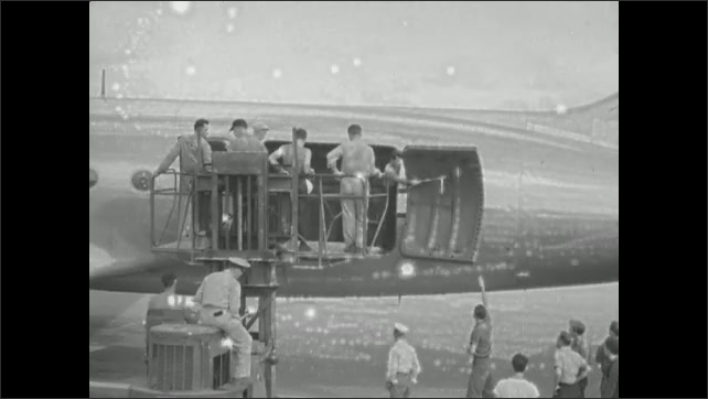 1940s: Man opens door on tail of airplane. Lift rises to door of airplane. Naval Supply Depot.