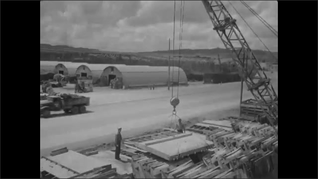1940s: Large platform hangs on crane. Crane moves platform. Platform hangs on crane.