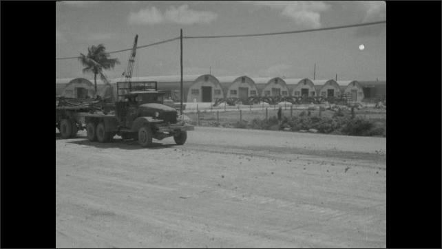 1940s: Person holds up clapboard. Military truck drives down road and pulls up to Naval Supply Depot.