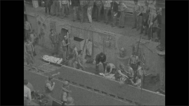 1940s: Wounded person on stretcher is lowered by crane onto deck of battleship. Wounded person on stretcher is transferred by crane from destroyer to battleship.