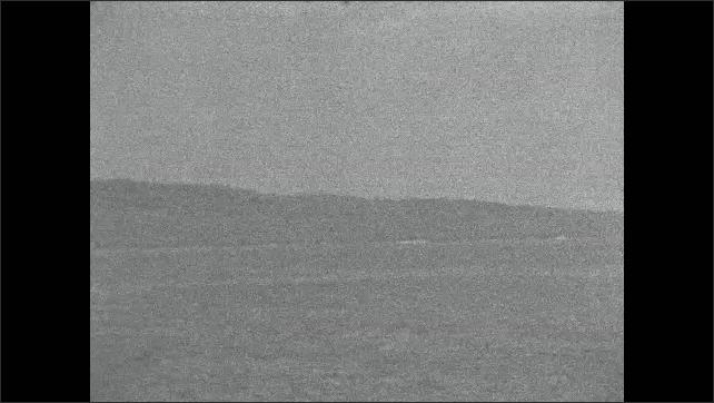 1940s Iwo Jima Japan: Artillery shells explode on shore of Iwo Jima.