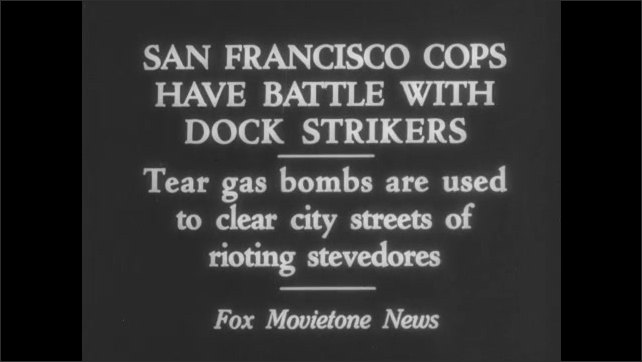 1930s San Francisco: Police fight striking dock workers, use tear gas bombs. Busy street, large crowds of people on sidewalks, men on horses, overturned truck, boxes spilled.
