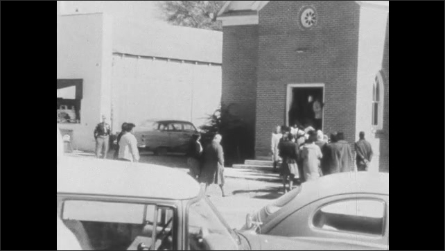 1960s: Group of people stand by side of road with police officers. Officers help people cross street to church. People wait to enter church.
