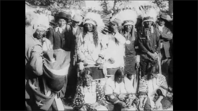 1910s: Two men address Native Americans standing next to soldiers.