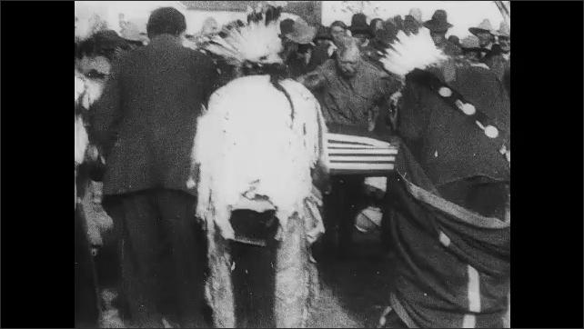 1910s: Native American men listen to white men speak to them. Intertitle. Native Americans bow around flag.