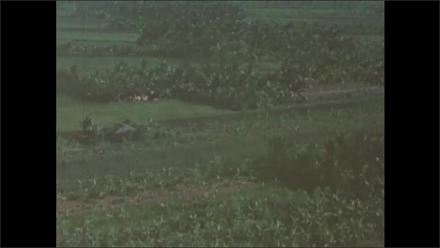 1960s Vietnam: Aerial view of Mekong River Delta. Helicopter flies over jungle, rice paddies and fields in Vietnam.