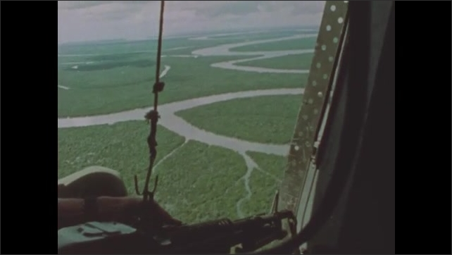 1960s Vietnam: Helicopter flies toward shoreline. Helicopter gunners look down on Mekong Delta valley.