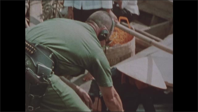 1960s Vietnam: Soldiers toss rope to Vietnamese civilians in rowboat. Soldiers inspect passengers and goods on civilian boat. Soldier sweeps metal detector over goods on civilian boat.