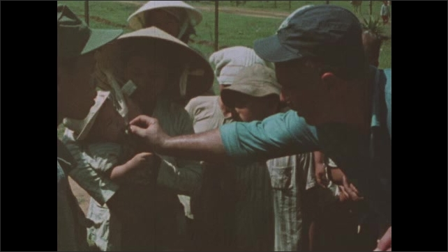 1960s Vietnam: Soldiers hand out chocolate bars and medicine to crowds of Vietnamese civilians in village.