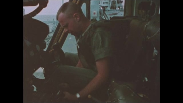 1960s Vietnam: Soldier preps cockpit of helicopter and speaks. Rotor blades of helicopter spin.