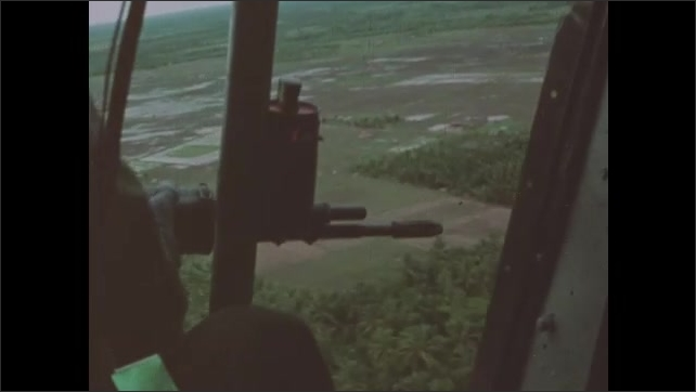 1960s Vietnam: Helicopter fires on shoreline. Helicopter gunner fires from open door on aircraft. Helicopters circle over patrol boats and shoreline.
