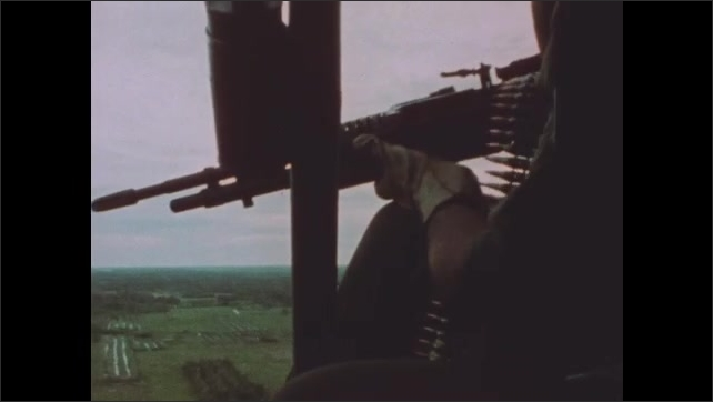 1960s Vietnam: Helicopter fires on shoreline. Helicopter gunner fires from open door on aircraft. Soldier waves to helicopters from patrol boat.