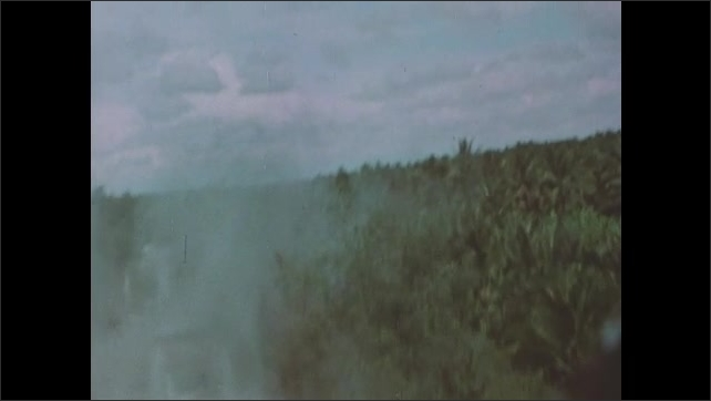 1960s Vietnam: Helicopter fires machine guns and rockets at river and shoreline. Water splashes from large explosion.