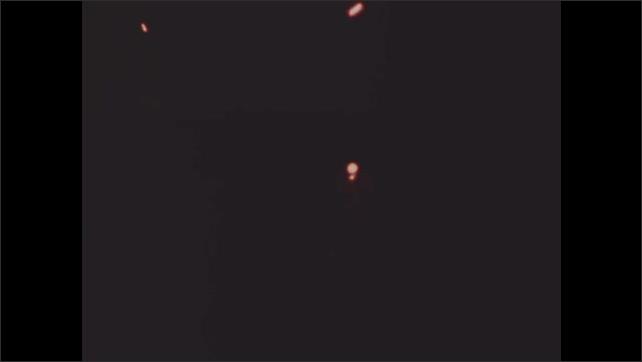 1960s Vietnam: Helicopter flies over Mekong River Delta at sunset. Tracer bullets streak through darkness.