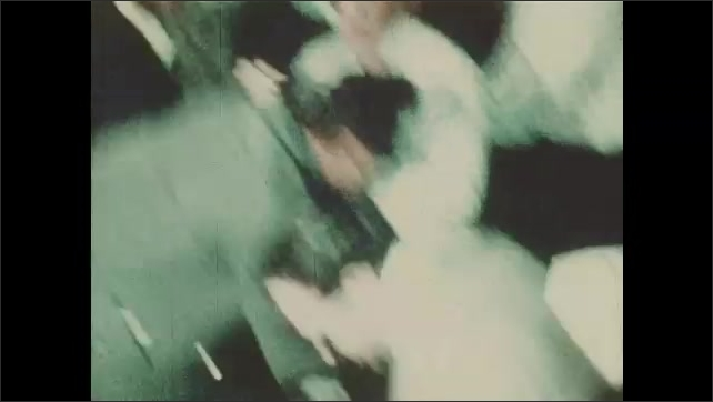 1968: Crowd of people bent over in panic. People waving in a direction. People in a panic in crowd.