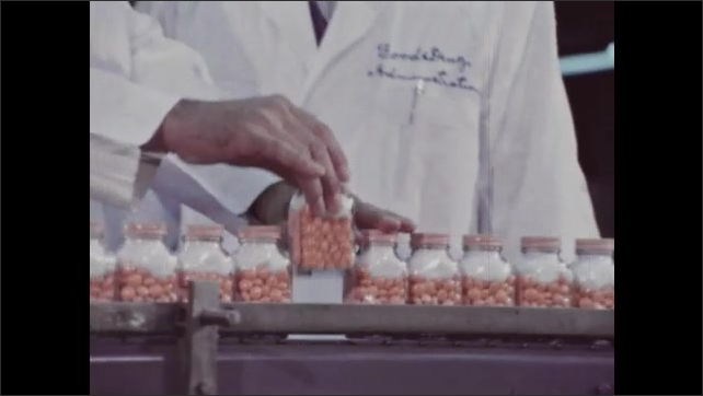 1960s: Man picks up plate containing pills, dumps pills in dish, and jots note on clipboard. Man in lab coat plucks bottle from row on conveyor belt and hands it to man. Man studies bottle. Men talk.