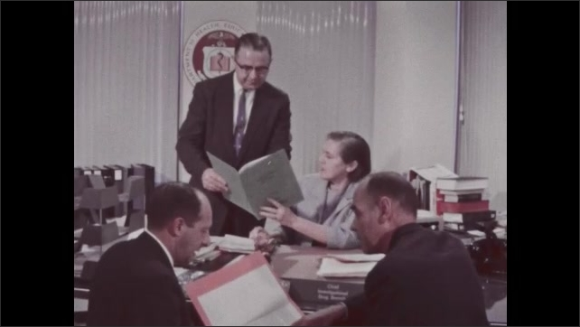 1960s: Sign for Department of Health, Education and Welfare. Man walks by. Men and woman speak.