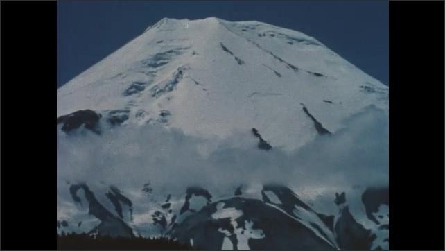1980s Washington: People stand at water's edge.  Rushing water.  Mount St. Helens.  Lake.