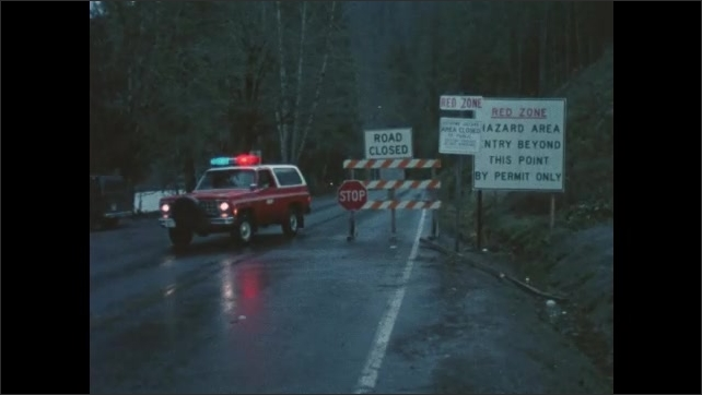 1980s Washington: Smoke comes out of crater on volcano.  Truck with flashing lights drives away from roadblock.  House.