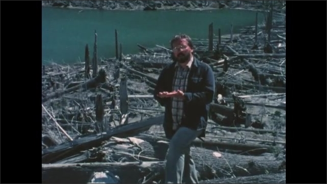 1980s Washington: Mountains covered with fallen trees.  Lake.  Man speaks and gestures.