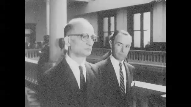 1960s: Members of the press take photographs and follow officials. Men lead Rudolph Abel down pillared hall. Man speaks and words appear beneath him. Words in box. Men stand by wall and speak.