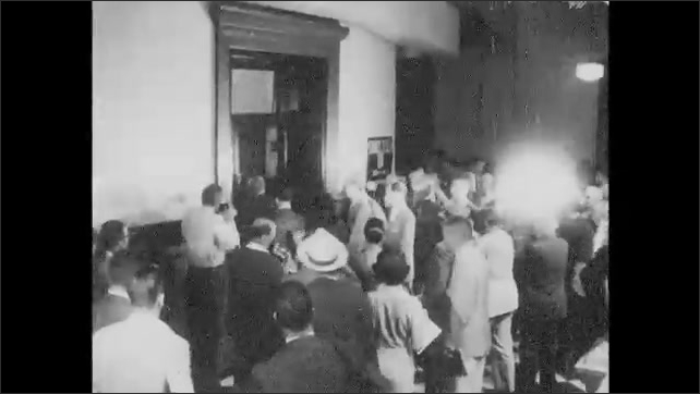 1960s: Man stands near wall and speaks. Men lead criminal into court room. Crowd gathers near court room doors and takes photographs. Sign on door. Men lead Rudolph Abel into court room.
