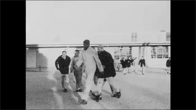 1960s: Prison complex on Alcatraz island. Prisoners walk through yard. Box and text appear over prisoners. Men work on industrial machines in prison rehab center.