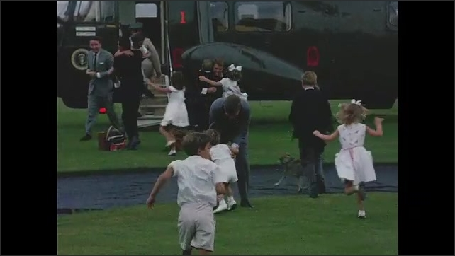 1960s: John F Kennedy and Robert Kennedy exit helicopter, children run toward helicopter, Kennedys hug children.