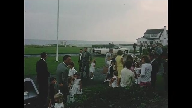 1960s: Members of Kennedy family standing outside house. John F Kennedy standing with children, family members talking in group.