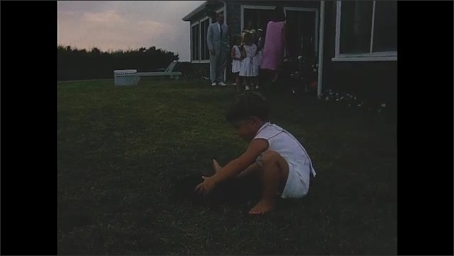 1960s: John F Kennedy Jr. playing with puppy. Kennedy sitting on ground, playing with puppy.