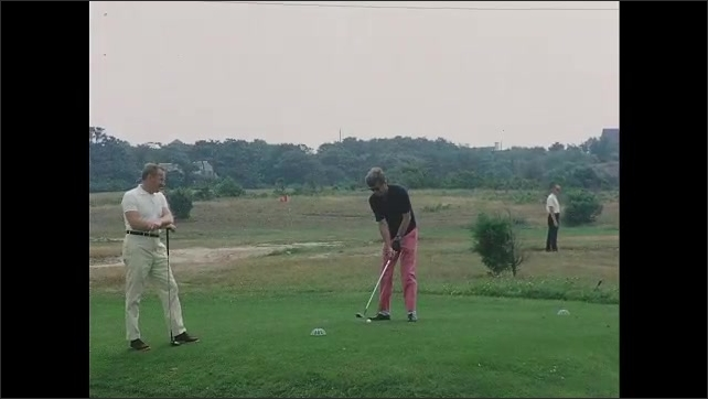 1960s: Long shot, John F Kennedy golfing with Paul Fay. Kennedy swings, hits ball.