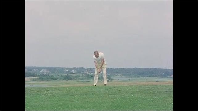 1960s: Slow motion, John F Kennedy swings club, hits golf ball. Paul Fay hits golf ball, caddies walk into frame.