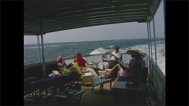 1960s: Caroline Kennedy crawling on floor of boat. John F Kennedy, Jacqueline Kennedy, Paul Fay and Anita Fay sitting on deck of boat.