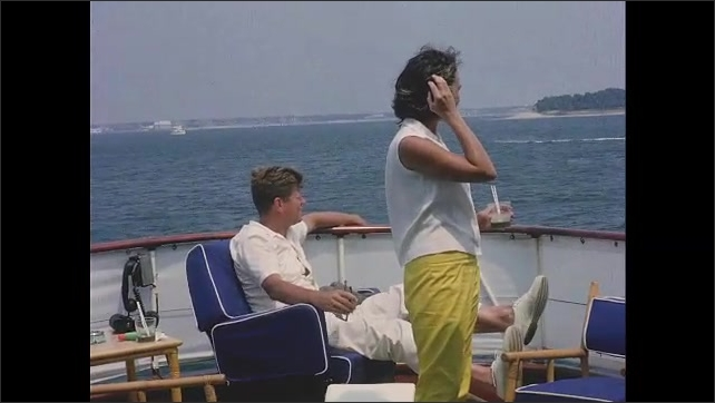 1960s: View of boat from deck of yacht. Bobby and Ethel Kennedy on boat, pan across Jacqueline Kennedy, John F Kennedy and others on deck. Boat pulls away, Kennedy and others wave.