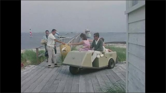 1960s: Long shot, people on pontoon boat. John F Kennedy, Jacqueline Kennedy and girls on golf cart, Kennedy drives cart on walkway.