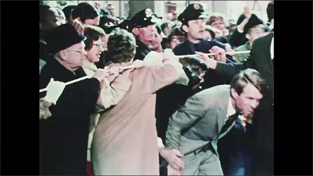 1960s Oregon: Crowd of people stand behind rope line. Robert F. Kennedy emerges from crowd, ducks underneath rope, waves, shakes hands with people in crowd.