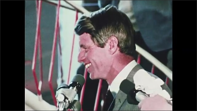 1960s Oregon: Robert F. Kennedy walks through crowd at mall, shakes hands with people. Kennedy stands at microphones, talks, jokes.