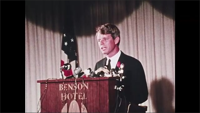 1960s Oregon: Robert F. Kennedy stands at podium, speaks. Cameraman walks behind Kennedy. Crowd watches and listens.