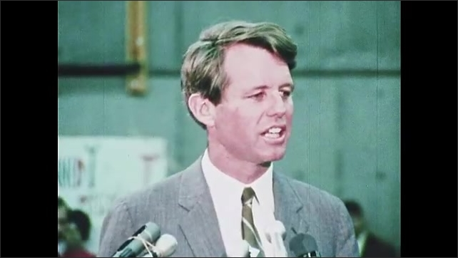 1960s Oregon: College students sit and listen to Robert F. Kennedy talk. Man takes photograph. Robert F. Kennedy stands at podium, speaks. Audience stands up, claps and cheers.