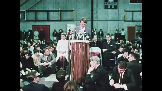 1960s Oregon: Audience claps and cheers. Robert F. Kennedy stands at podium, speaks.