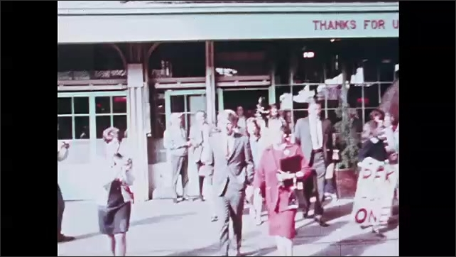 1960s: Robert Kennedy gives speech in banquet hall of Benson Hotel. Kennedy walks across train station platform, shaking people's hands. Kennedy on back of train.