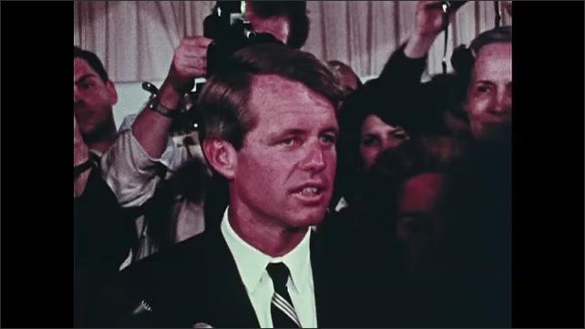 1960s: Robert Kennedy speaks to crowd of people in room surrounding him.