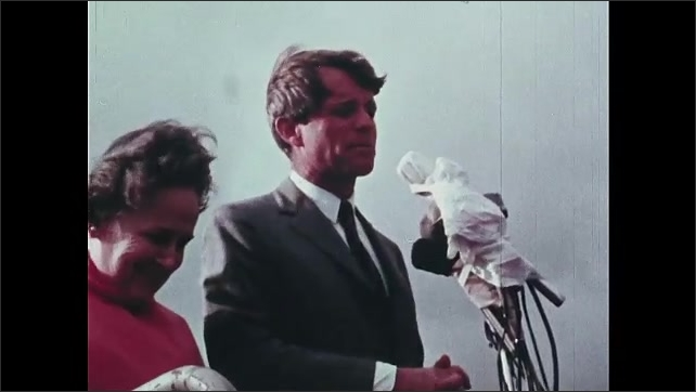 1960s Oregon: Robert F. Kennedy gives outdoor speech.  Man speaks and gestures.  Woman waves.