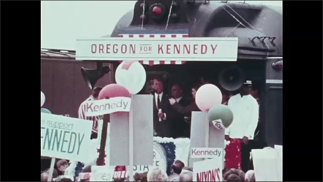 1960s Oregon: Robert F. Kennedy speaks from back of train. Crowd.  People hold signs.