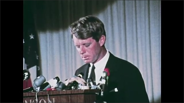 1960s Oregon: Robert Kennedy with red rose in his lapel speaks at podium with microphones and U.S. flag in background