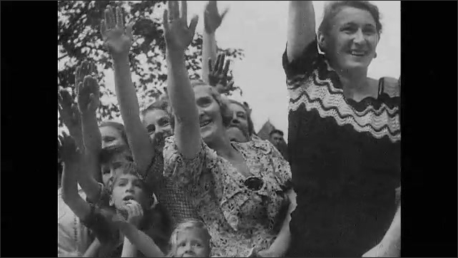 1930s Germany: Adolf Hitler greeting and walking through crowd, cars driving in parade surrounded by cheering crowds