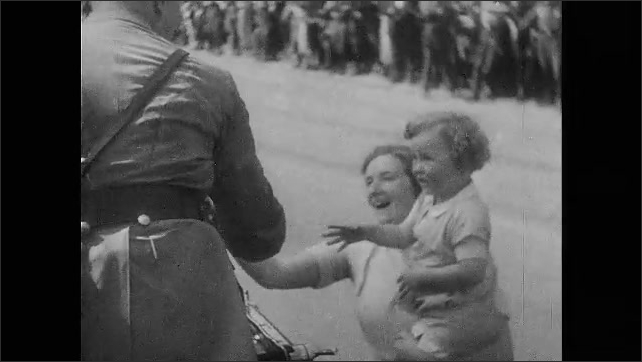 1930s Germany: Adolf Hitler waving to cheering crowds from car in parade, statue surrounded by iron fencing, Hitler shaking hands with young girl and sister, children smiling