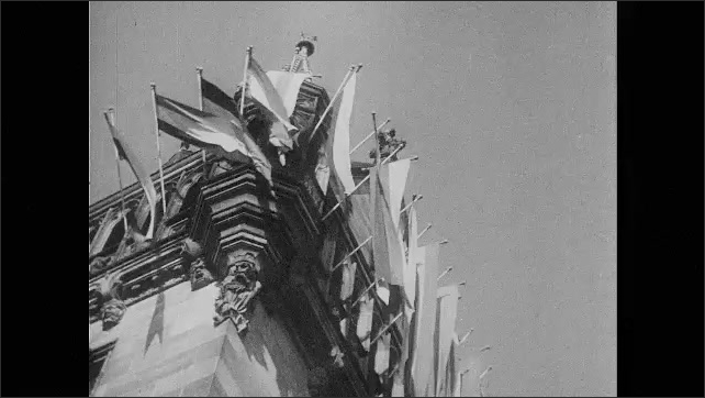1930s Germany: Nazi flag hanging behind statue, buildings with flags waving as parade passes by, Hitler standing in car overlooking crowds
