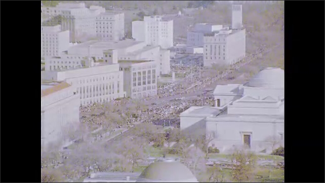 1960s: Crowds of people walk down the street.