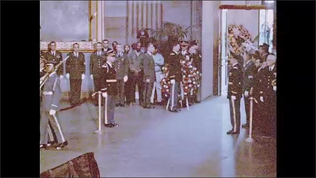 1960s: Men in uniform carry American flag into Capitol building rotunda. Men in uniform carry casket into rotunda.